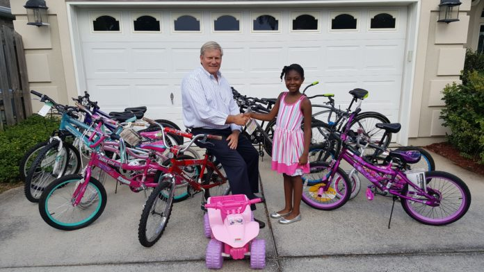 Photo L to R: Ken Hair, CIC President & CEO receives a $300 donation of bikes for the children living at the Children in Crisis Neighborhood from nine-year old Marlee Green. For the second year, Marlee donated gifts from her recent birthday party to the children living at the CIC Neighborhood.